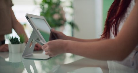 Female store owner completing purchase with customer using a tablet in interior boutique clothing store with soft day lighting. Close up on 4k RED camera.
