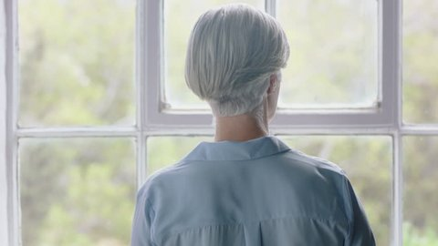 old caucasian woman drinking coffee at home enjoying successful retirement looking out window planning ahead middle aged female thinking contemplating retired lifestyle