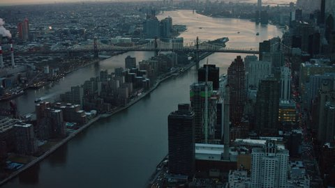 Aerial view of the East River and Roosevelt Island, New York City, dark sunset lighting. Wide shot on 4k RED camera.