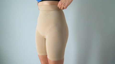 Woman in slimming panties wears a blue dress on top and checks the result. Concept of aspiration for a perfect body
