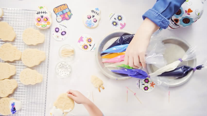 Step by step. Flat lay. Mother and daughter decorating sugar skull cookies with royal icing for Dia de los Muertos holiday. | Shutterstock HD Video #1018591312