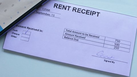 Rent receipt document paid, hand stamps seal on official paper, regular payment