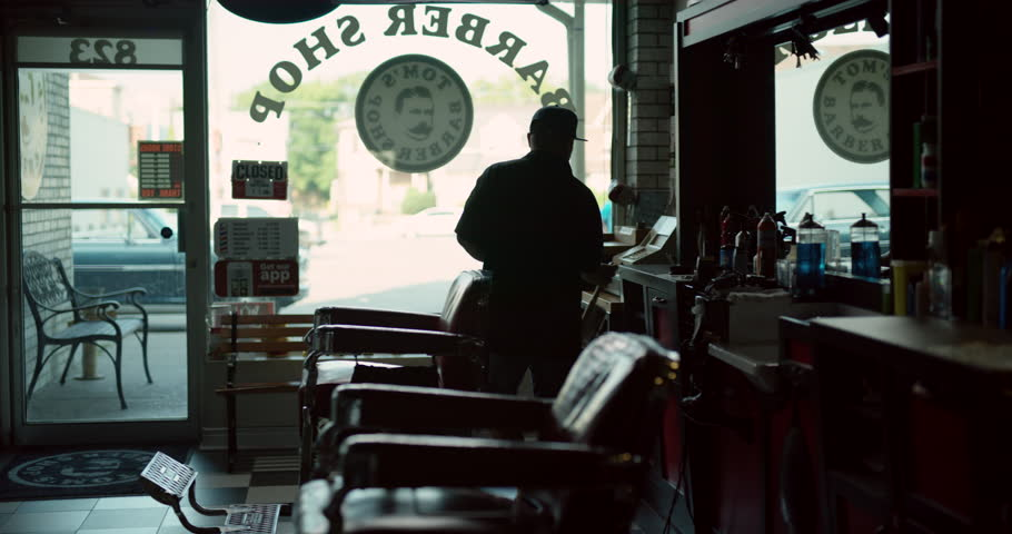 Trendy hair stylist getting shop ready for business in interior hipster barbershop with dim day lighting. Wide shot on 4k RED camera.   Shutterstock HD Video #1018616362