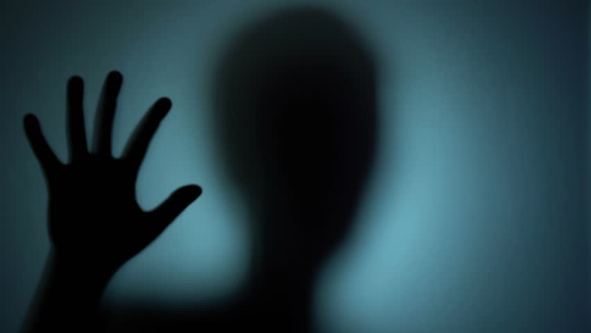 Mental hospital patient behind the glass, creepy silhouette, horror scene. Blood-chilling horror thriller shot   Shutterstock HD Video #1018622332