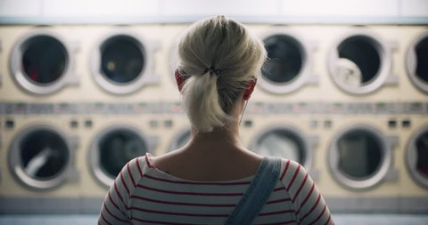 Young woman sitting in a chair and watching the laundry machines running in interior small laundromat with bright interior lighting. Wide to Medium shot on 4k RED camera on a gimbal.