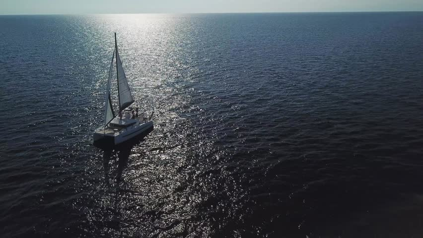 Aerial front side view of Catamaran sailboat sailing in full sail on a dark blue sea with reflexes in backlight | Shutterstock HD Video #1018644832