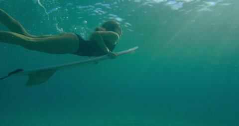 Professional female surfer diving under ocean water with surfboard in Australian beach with bright day lighting. Wide shot on 4k RED camera.