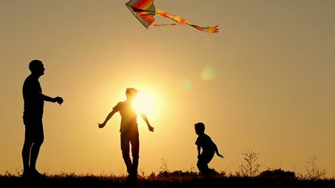 Happy father runs the snake into the air. Two children are playing, frolicking and jumping over a kite. Family unity, outdoor recreation.