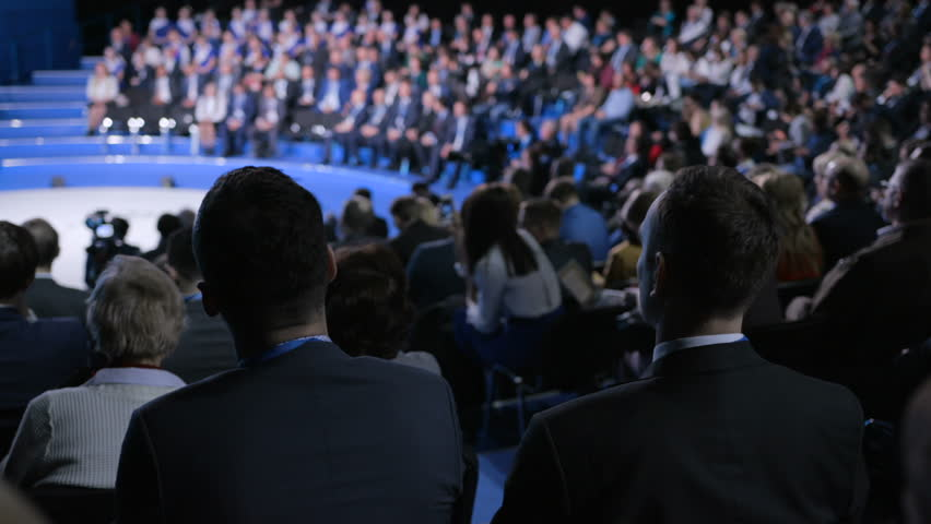 Male entrepreneur at crowded forum for banking leadership or trading collaboration. Information concept for development idea of sale indoors. Row of seats in large place for worker expert or spectator   Shutterstock HD Video #1018757332