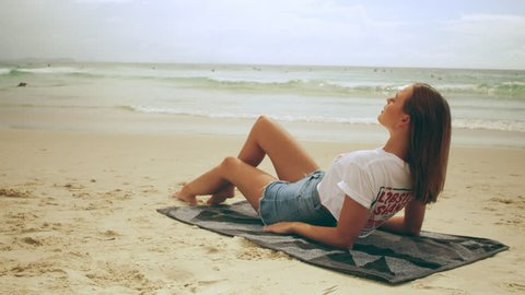 Beautiful young strawberry blonde woman wearing cut off jean shorts and t-shirt lays on a towel on the beach on Australian summer day. Medium shot in 4K on a RED camera.
