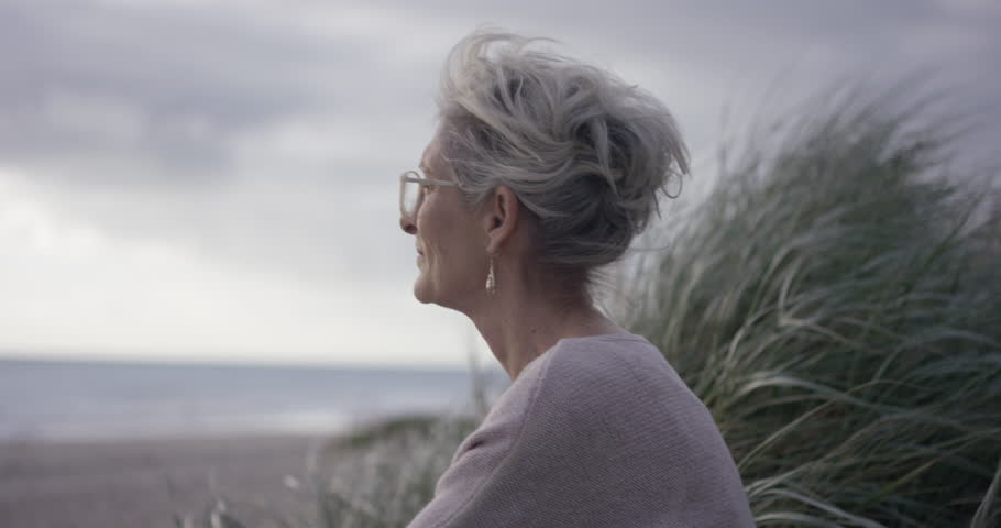 Mature lady sitting and looking out at ocean contemplating life | Shutterstock HD Video #1018780882