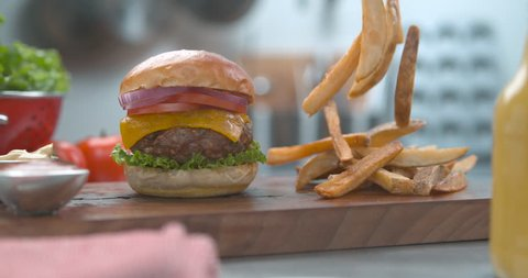 Delicious hamburger and salty fries falling onto a wooden board on a table with bright studio lighting. Close up slow motion shot on 4k phantom fles camera.