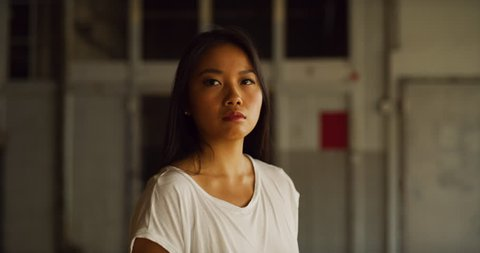 Graceful asian dancer pirouettes in industrial wood and brick windowed loft during daytime. Wide to long shot on 4K RED camera.