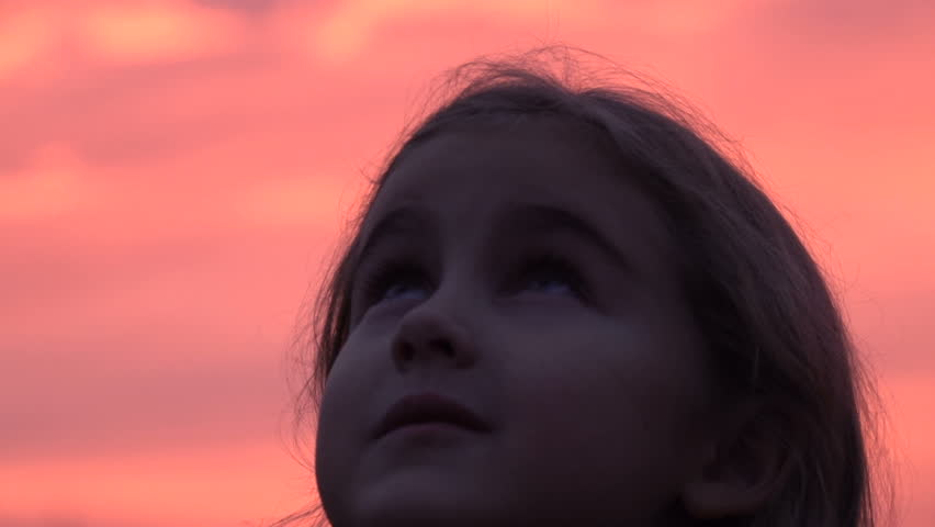Kid looking up at the sky in nature. Little girl praying looking up at purple sky with hope, close-up.