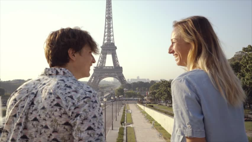 Young couple making heart shape finger frame with hands against the Eiffel Tower in Paris city France. Two people young adults enjoying loving the vacations in Europe and having fun | Shutterstock HD Video #1018850452