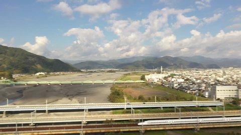SHIZUOKA, JAPAN - OCTOBER 26TH, 2018. Aerial view of Japan high speed bullet train crossing the bridge at Shizuoka City.