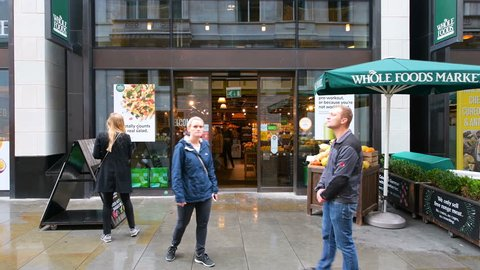 London, UK - September 12, 2018: Wide angle view on Whole Foods Market, Wholefoods store, shop entrance on Glasshouse street with many people, pedestrians walking in rain, raining with umbrellas