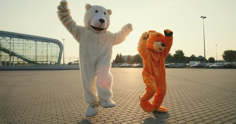 Two funny and cute big growth dolls of bears running, dancing and having fun outdoor.