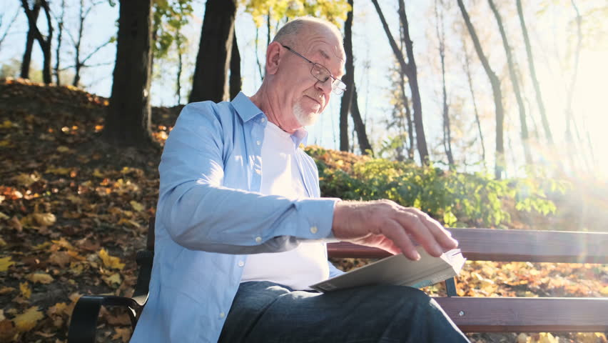 Portrait shot of the senior man with beard in glasses reading a book, while having rest in the park. Senior father reading book