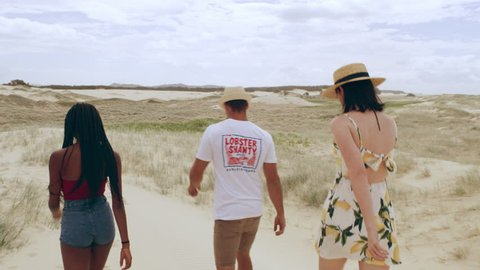 Group of friends having walking along sand dunes stopping to take in view of beautiful beach in Australia. Wide shot on 4k RED camera.