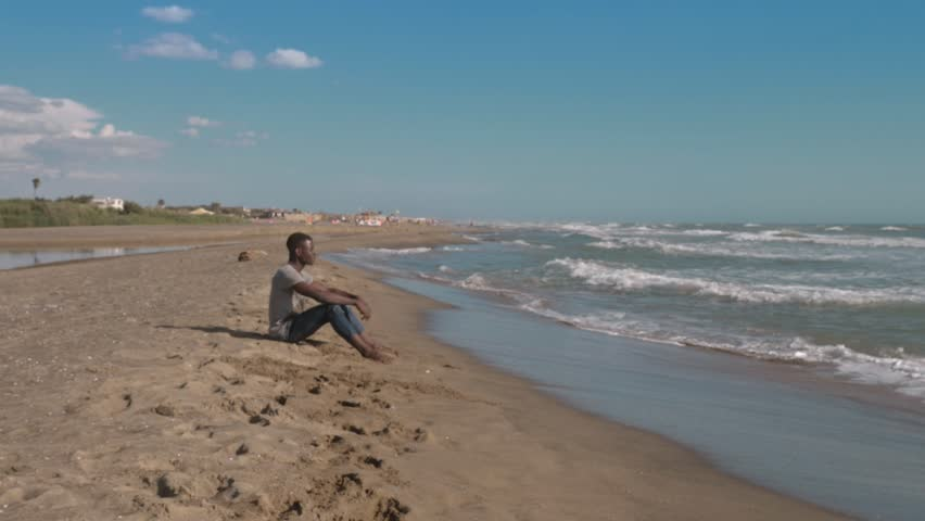 Peace, nature, relax. Young black american sitting on the beach observing ocean | Shutterstock HD Video #1018958212