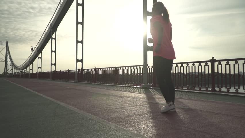 Lovely girl is running on the bridge in the morning. Slow motion #1018963702