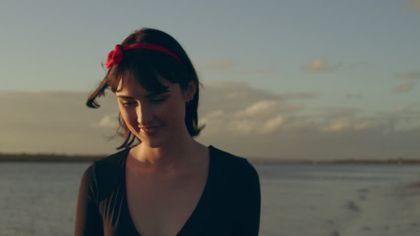 Woman walking along beach smiling as sun sets behind her in Australia.Medium close on 4k RED camera.
