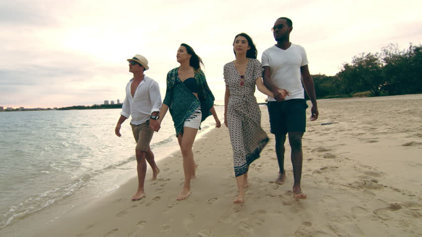 Two attractive couples, holding hands, walking on the beach, talking and smiling, under a cloudy sky. Close to wide shot on 4K RED camera.