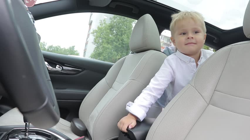 The kid sits in salon of the car on back sitting. dabbles with the armrest. throws a toy there | Shutterstock HD Video #1018972372