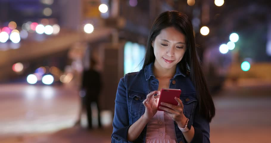 Woman use of mobile phone in city at night | Shutterstock HD Video #1018987072