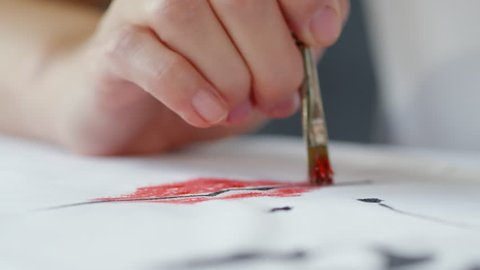 Close up shot of hand of unrecognizable artist with paintbrush dabbing red color on white fabric while creating image of female face for custom design clothes