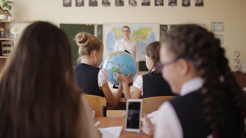 High School Students Study Globe During Geography Lesson