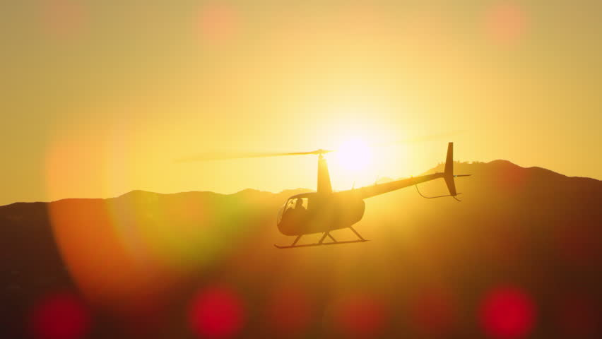 Aerial view of helicopter flying over mountains into the clouds during magical sunset in Los Angeles, California. Wide long shot on 4K RED camera. #1019021902