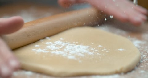 Sprinkled flour drops onto dough being rolled with rolling pin, in soft focus, in soft light, in slow motion. Closeup shot in 4K on Phantom Flex.