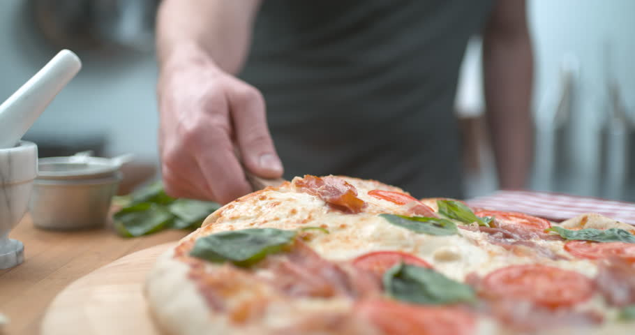 Freshly baked wood fired pizza being sliced and served with melty cheesy closeup ultra slow motion with 4k Phantom Flex camera.