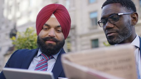 Two diverse males in suits checking newspaper and tablet for financial information