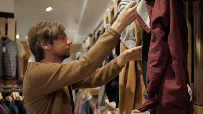 Man chooses sports clothes in a store shopping mall young student casual clothing buy checkout paying | Shutterstock HD Video #1019041912