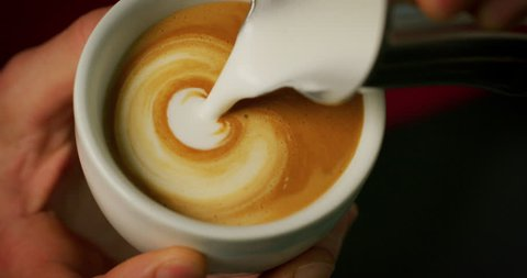 Macro of a barman while drawing with the froth the cappuccino in a typical italian bar. Concept: Concept: art, passion, love