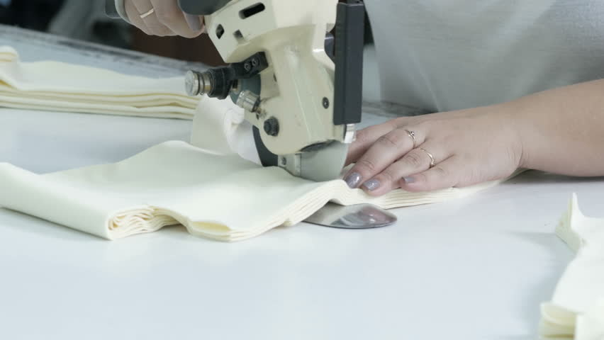 Cutting the fabric, sewing work. Cutting room, woman cutting light beige cloth tailoring knife. | Shutterstock HD Video #1019059912