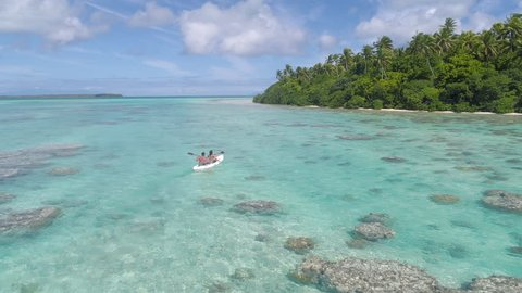 Aerial - Couple paddling in canoe on crystal clear water with corals next to remote island with lush palm trees in French Polynesia