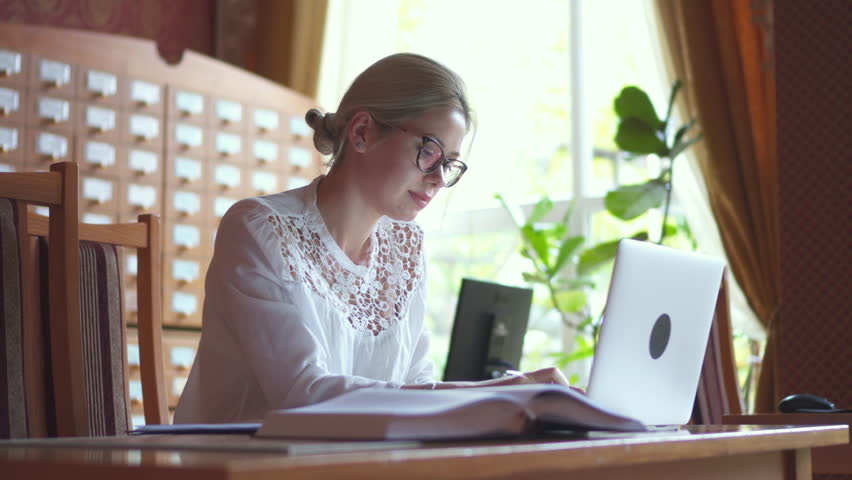 Woman using laptop and looking at textbook in library | Shutterstock HD Video #1019127832
