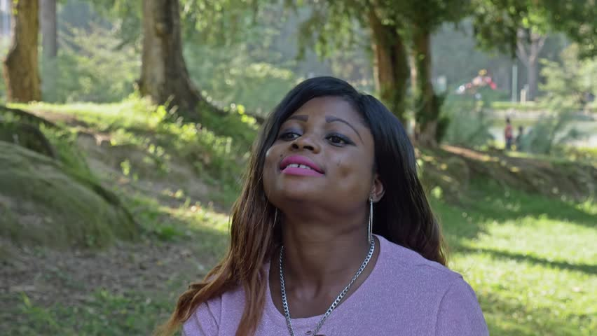 Smiling african american woman walking in the park- slow motion   Shutterstock HD Video #1019146402