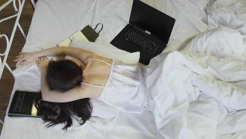 Hd00 05young Woman Sleeps Prone Near Laptop And Tablet On Bed