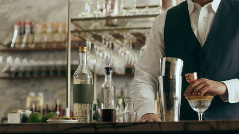 Flair artist flips bottle in the air then pours alcohol into a shaker in a beautiful modern trendy bar. Close shot on a RED camera.