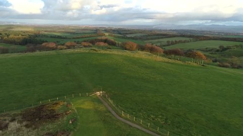 Cairnpapple Hill, near Torphicen in West Lothian, Scotland. A Neolithic ceremonial henge monument. Aerial footage flying away to reveal its place in the landscape.
