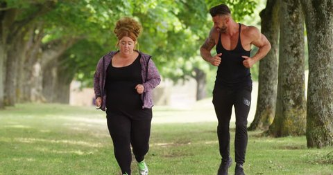 4K Overweight unfit woman running in the park with personal trainer, exhausted but encouraged by him to carry on.