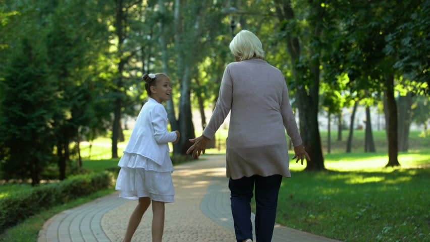 Excited girl telling grandmother stories during walk in park having fun, gossips | Shutterstock HD Video #1019232022