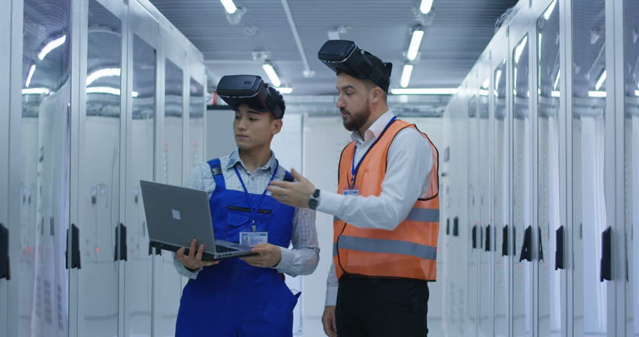Medium shot of electrical workers in reflective vests using VR headsets and a computer in the control room of an electrical station | Shutterstock HD Video #1019245702