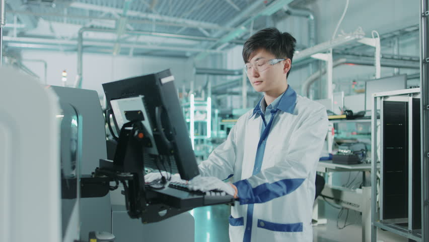 On High Tech Factory Asian Engineer Uses Computer for Programming Pick and Place Surface Mount Electronic Machinery for Printed Circuit Board Assembly Line.Shot on 4K (UHD) Camera | Shutterstock HD Video #1019311732