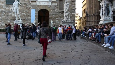 PIAZZA DELLA SIGNORIA, FLORENCE, ITALY - 10 November 2018: People visit Palazzo Vecchio and admire the copy of Michelangelo's David and the Hercules and Cacus statue. HD Video